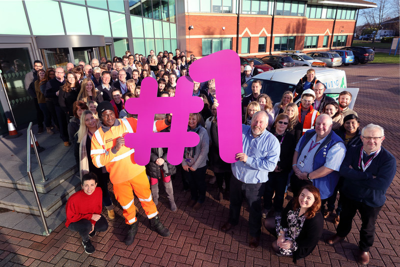 Group photo of Anglian Water employees outside Huntingdon office holding large Number One sign