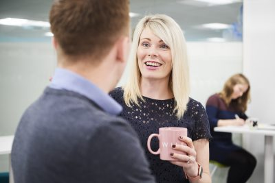 A female worker standing in an office, holding a mug and smiling whilst speaking to a male coworker in the foreground whose face is not visible