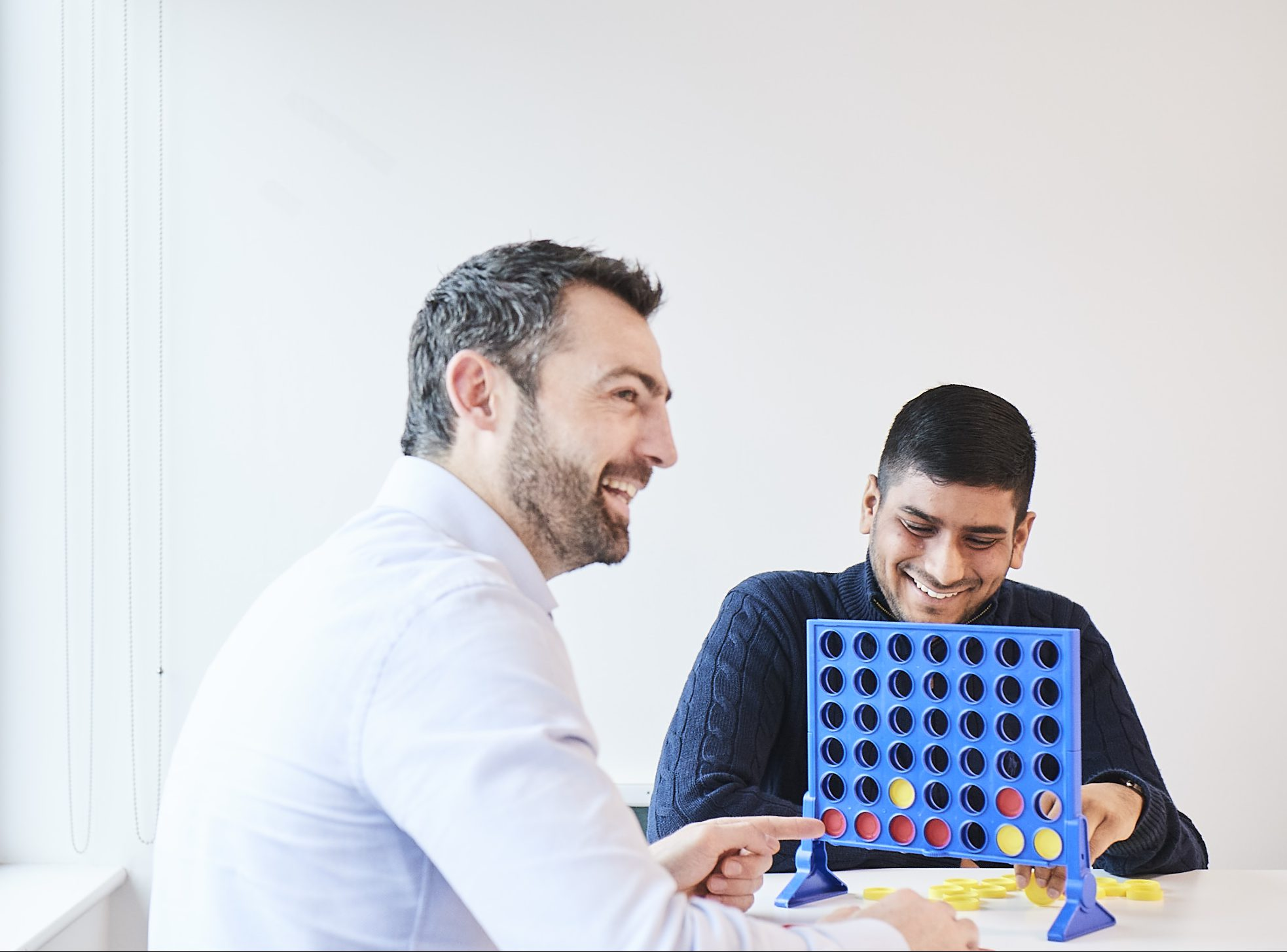 Close up shot of two male colleagues sitting at a table playing connect 4