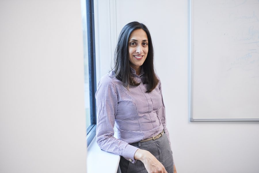 Smiling woman leaning against a windowsill in a conference room