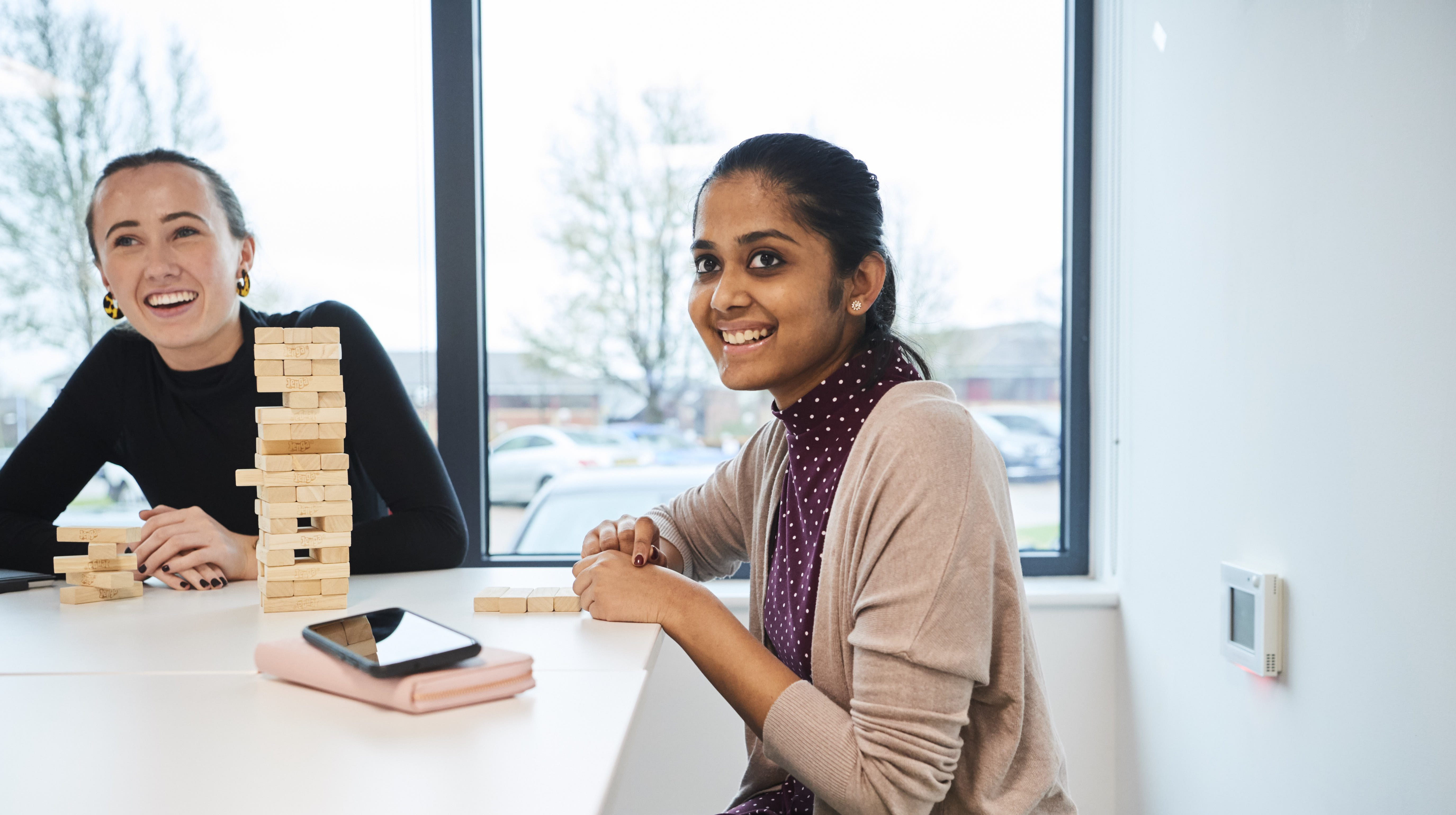 Two female co-workers sitting at a table playing jenga