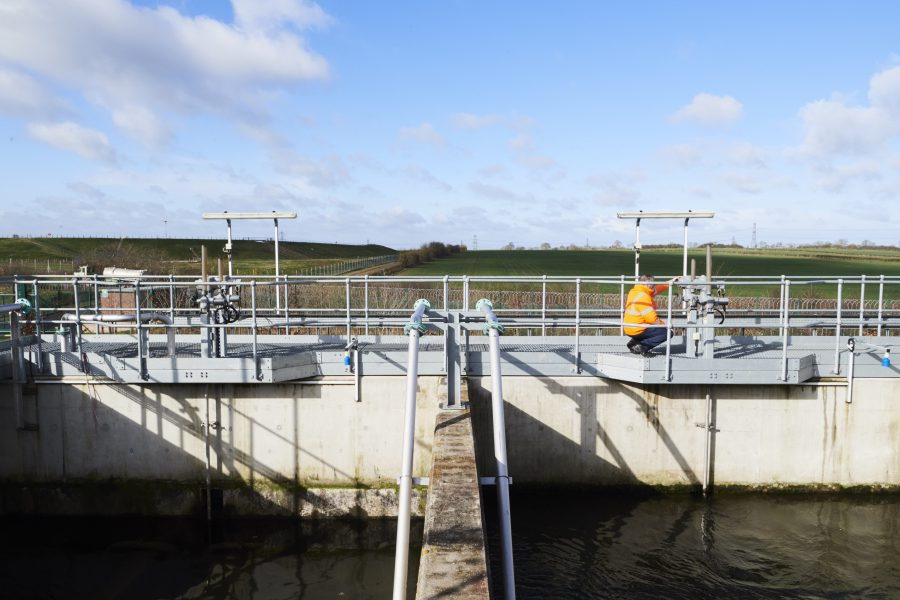 Male in high vis jacket on top of water treatment building checking gauges