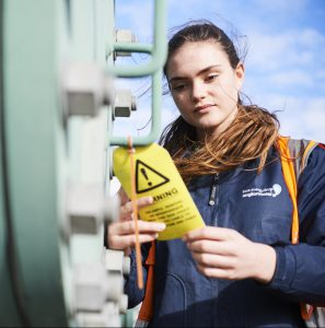 Close up from below shot of female apprentice in high vis jacket looking at yellow warning label on machine outside
