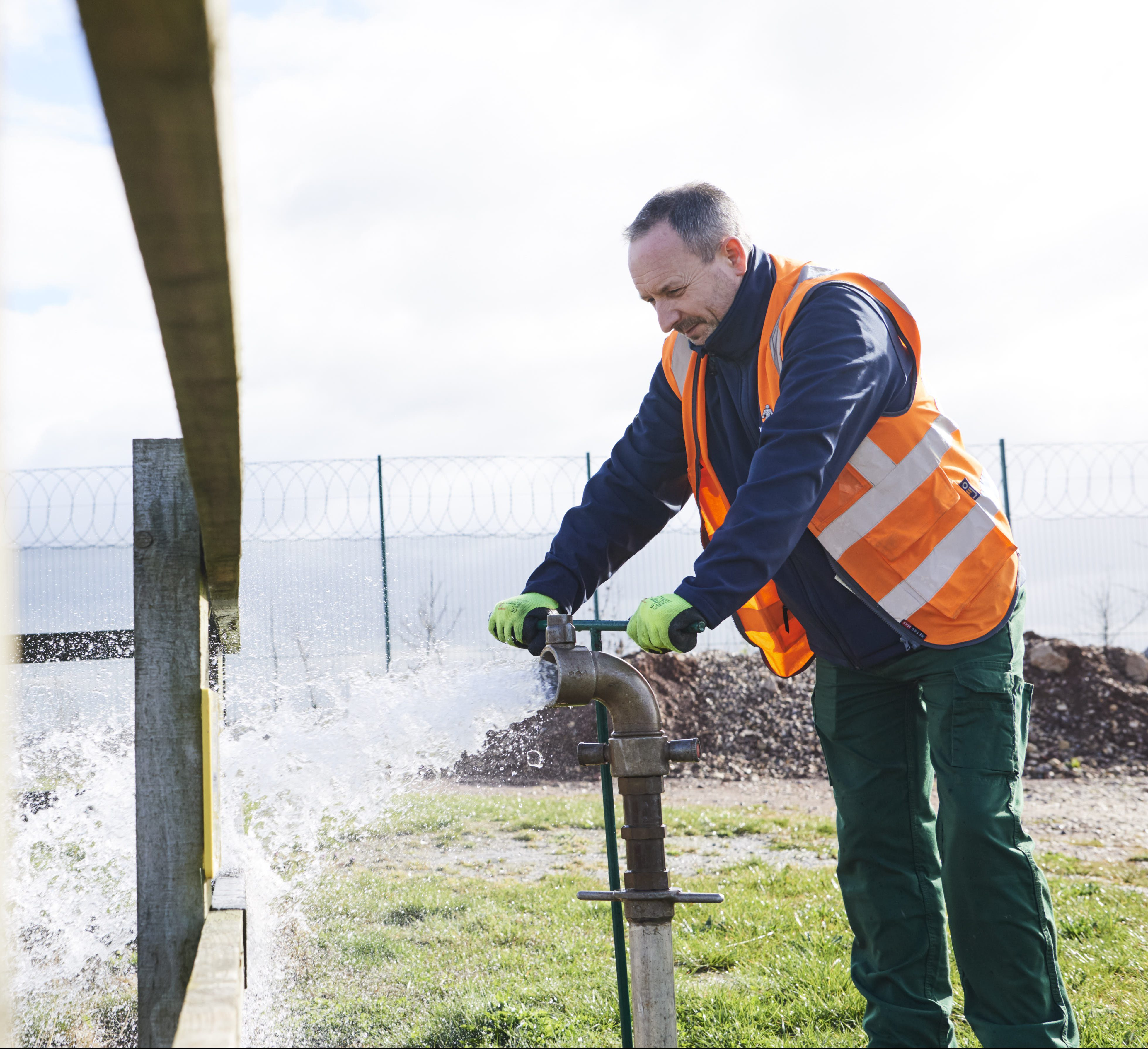 Male in high vis jacket at water treatment plant turning a water pipe