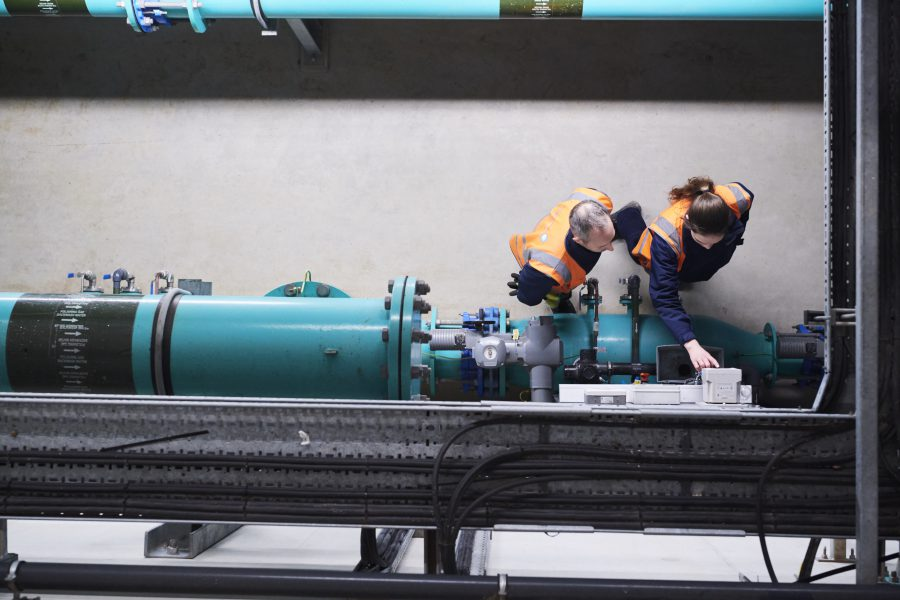 Overhead shot of male and female in high vis jackets pushing buttons on water pipe at water treatment centre