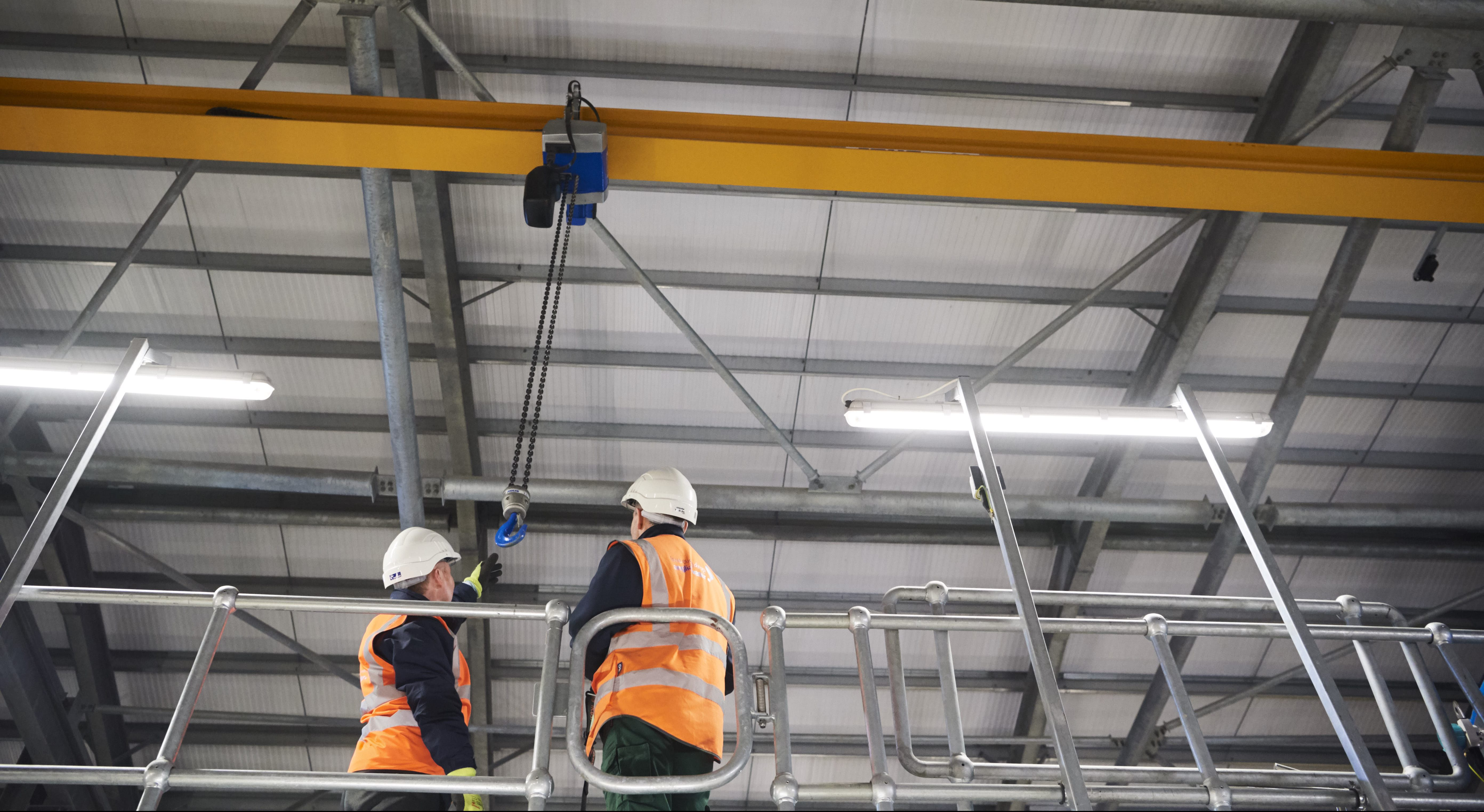 Shot from below of two males in high vis jackets and hard hats reaching from a hook on a crane