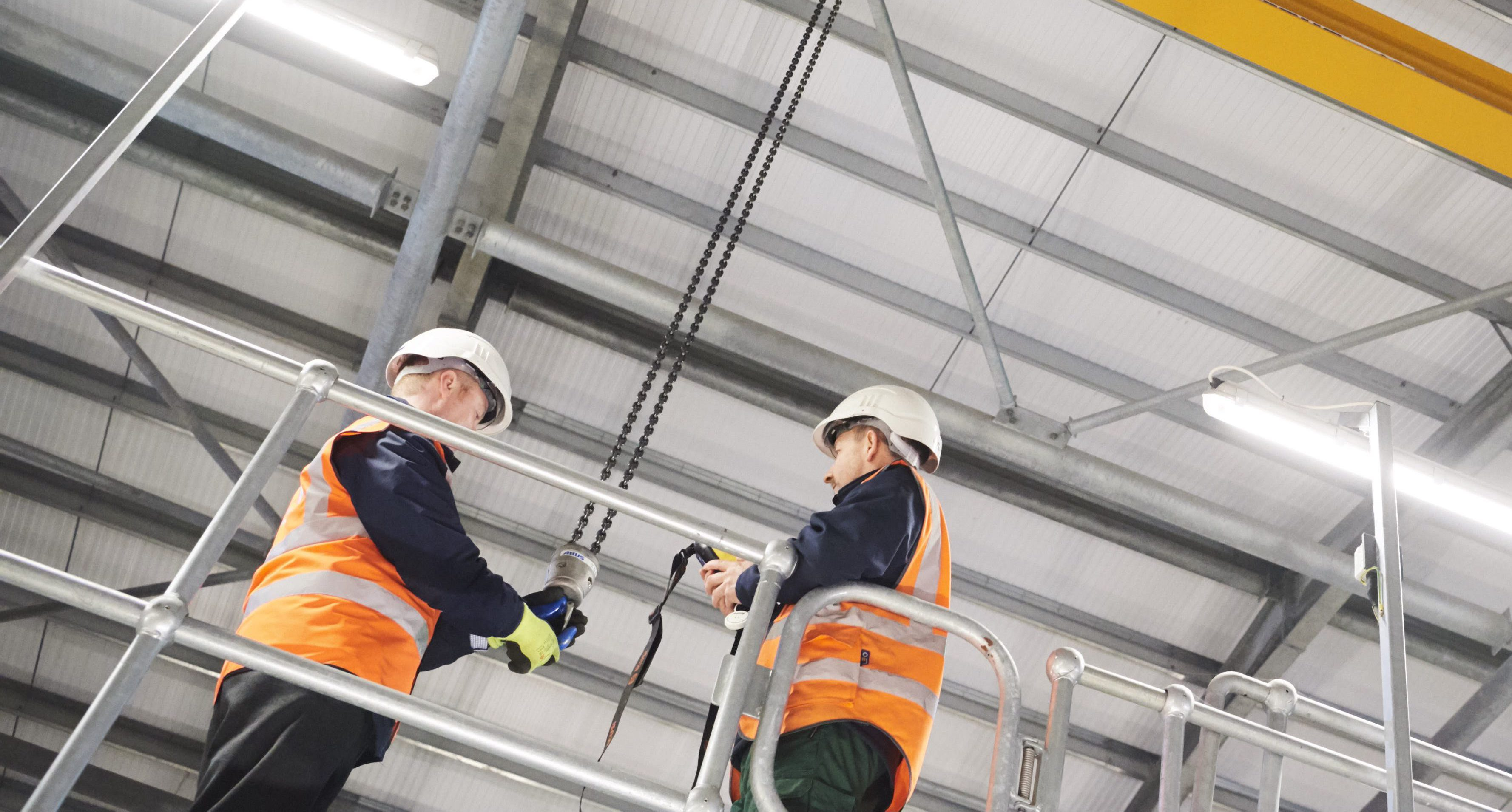 Looking up at 2 male colleagues - both in hard hats and helmets, one holding a hook on a chain dangling from the facility ceiling