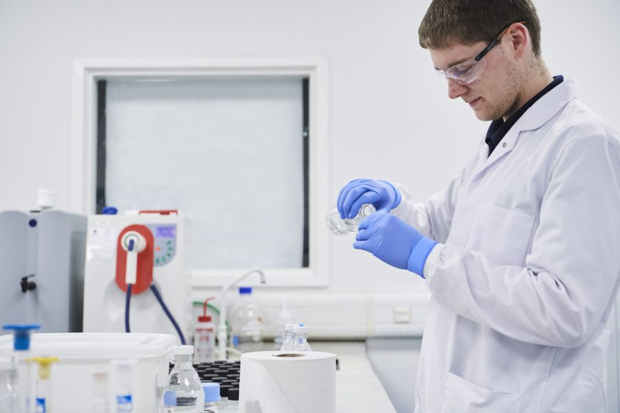 Male in laboratory environment with lab coat and gloves pouring one liquid into an unseen container