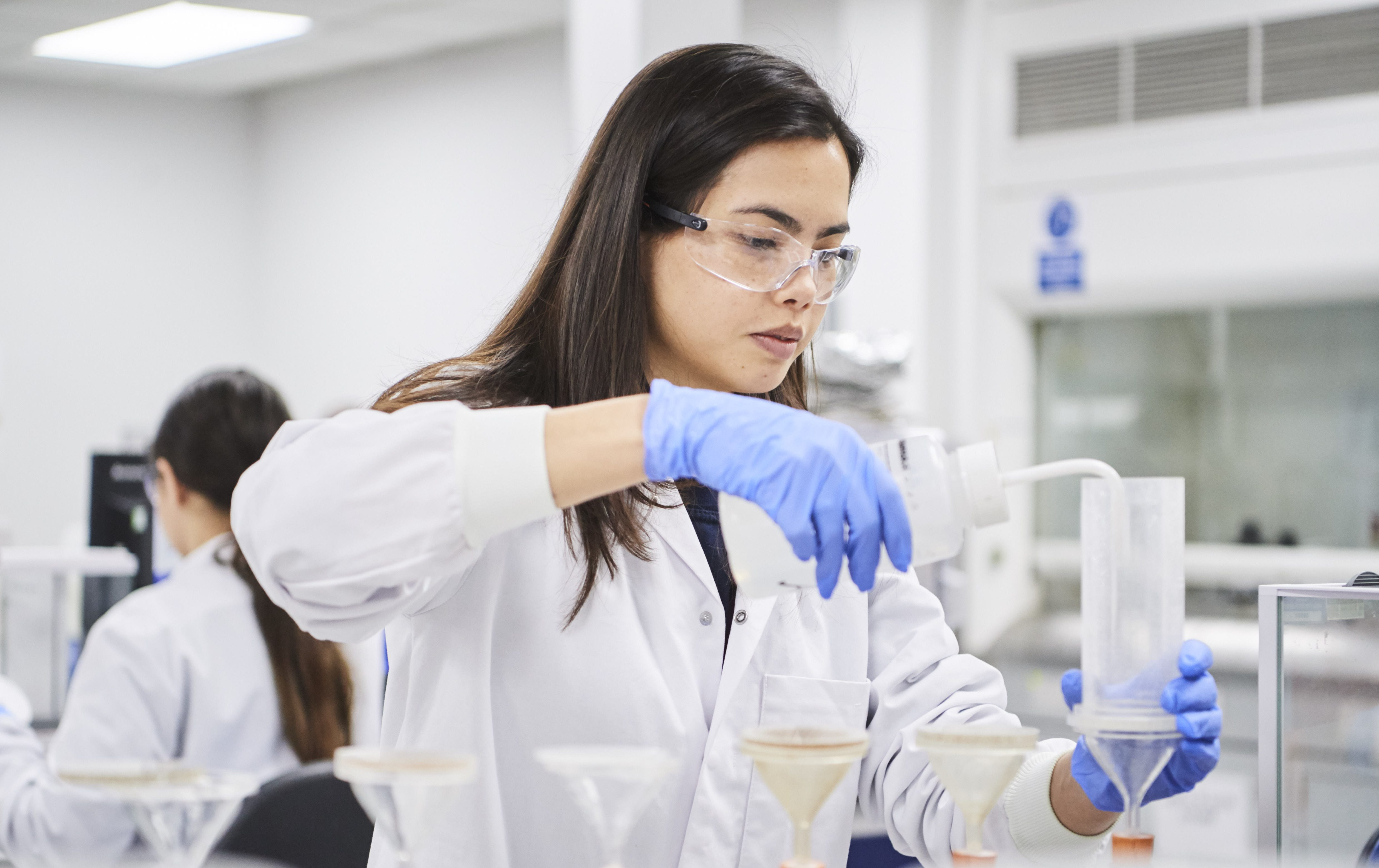 Female in lab environment in lab coat and gloves transferring liquid into a funnel
