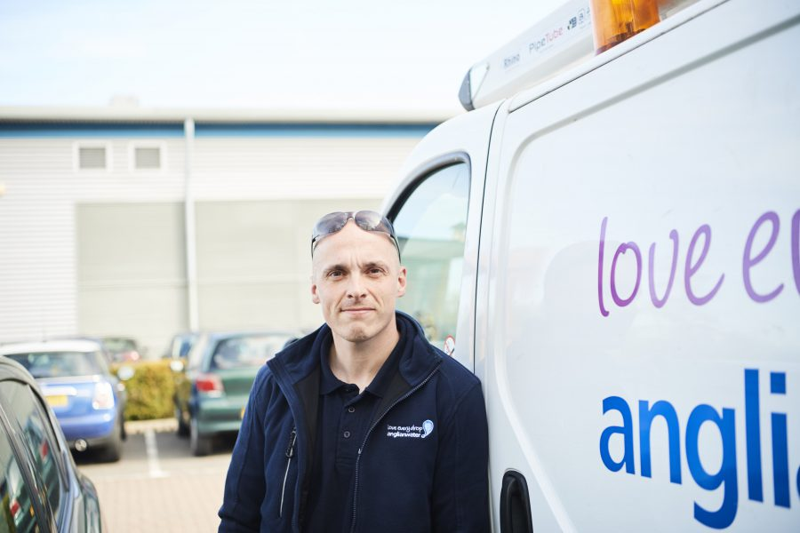 Male Anglian Water employee looking at the camera beside his Anglian Water van