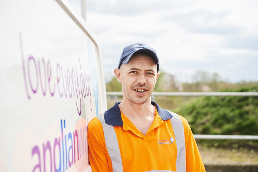 Head and torso shot of a man in a high vis top leaning against an Anglian Water van
