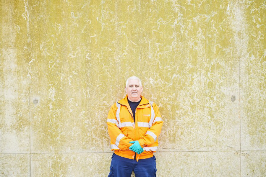 Shot of a man in a high vis coat and hygienic gloves leaning against an old wall at a treatment facility