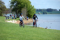Two people on bicycles riding on the grass next to a reservoir