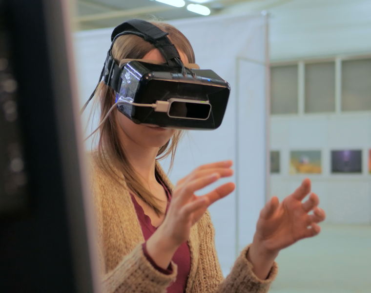 Woman in an office environment wearing a VR headset, hands out in front of her