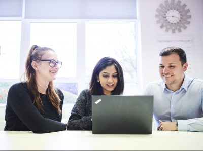 Two female and one male in an office environment looking at a laptop